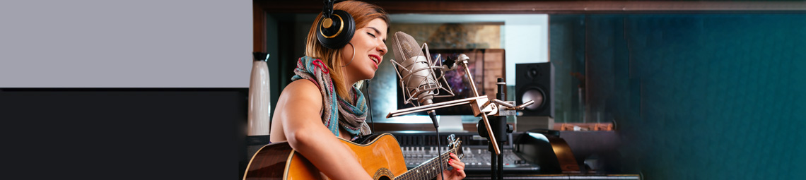 girl playing guitar in a recording studio
